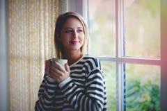 Jong meisje met kop van koffieverblijf dichtbij venster royalty-vrije stock fotografie