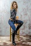 Jong meisje met krullend haar in een zwart overhemd, jeans en een hoge westelijke stijl van de laarzencowboy Stock Afbeelding