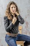 Jong meisje met krullend haar in een zwart overhemd, jeans en een hoge westelijke stijl van de laarzencowboy Royalty-vrije Stock Fotografie
