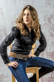 Jong meisje met krullend haar in een zwart overhemd, jeans en een hoge westelijke stijl van de laarzencowboy Royalty-vrije Stock Foto's