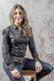 Jong meisje met krullend haar in een zwart overhemd, jeans en een hoge westelijke stijl van de laarzencowboy Royalty-vrije Stock Afbeelding