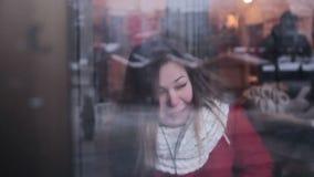 Jong meisje met lachen van tabletpc uit luid door het venster stock videobeelden
