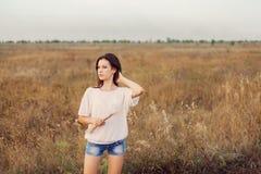 Jong meisje met lang bruin haar die zich bij de de herfstweide bevinden Stock Foto