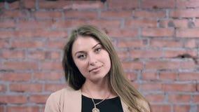 Jong meisje met lang haar, knipoogje door grote ogen in camera afgietsel Bakstenen muur stock footage