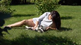 Jong meisje met lange haarspelen met een kleine hond in het park op het gras die een goede stemming hebben Langzame Motie HD stock video