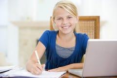 Jong meisje met laptop die thuiswerk doet Stock Foto's
