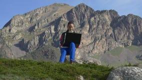 Jong meisje met laptop op de achtergrond van formidabele klippen stock videobeelden