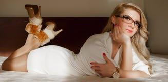 Jong meisje met met witte minirok die op het bed liggen royalty-vrije stock foto's