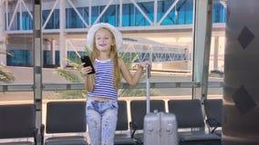 Jong meisje met mobiele telefoon en koffer die in vertrekzitkamer wachten in luchthaven stock videobeelden