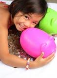 Jong meisje met muntstukken en spaarvarken stock fotografie