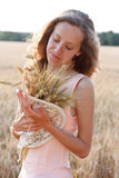 Jong meisje met rijpe tarweoren in de handen Stock Foto's