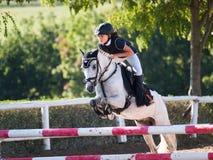 Jong meisje met roan poney op hindernis bij het showjumping van de concurrentie Royalty-vrije Stock Afbeeldingen