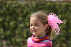 Jong meisje met roze veren in haar haar stock foto