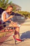 Jong meisje met skateboard en hoofdtelefoons het kijken Royalty-vrije Stock Afbeelding