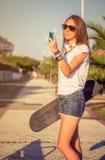 Jong meisje met skateboard en hoofdtelefoons het kijken Stock Foto's