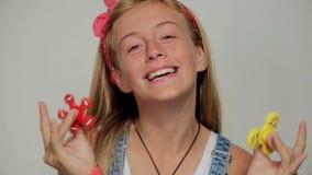 Jong meisje met spinners, een populair stuk speelgoed stock video