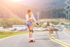 Jong meisje met stootkussens die op hellingsweg longboarding stock fotografie