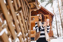 jong meisje met telefoon in vest tegen van houten plattelandshuisje royalty-vrije stock fotografie