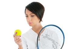 Jong meisje met tennisracket en geïsoleerde bal Stock Foto