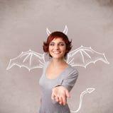 Jong meisje met van duivelshoornen en vleugels het trekken Stock Foto's