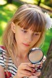 Jong meisje met vergrootglas in het park stock fotografie