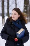Jong meisje met woordenboek en appel Stock Afbeeldingen