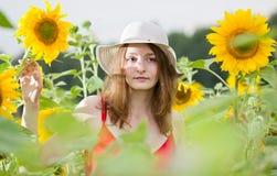 Jong meisje onder zonnebloemen Royalty-vrije Stock Foto's