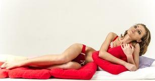 Jong meisje in ondergoed in bed schreeuwen en afvegende scheuren die haar handen smeren Stock Foto