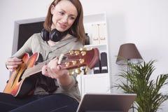 Jong meisje op bank het spelen gitaar Stock Fotografie