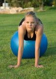 Jong meisje op blauwe geschiktheidsbal in het park Stock Foto's