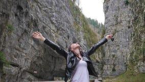 Jong meisje op de bergkloof, concept vrijheid, overwinning, actieve levensstijl stock footage