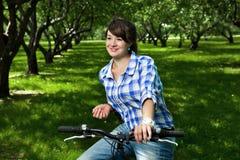 Jong meisje op een fiets in de tuin Royalty-vrije Stock Afbeelding