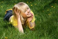 Jong meisje op een open plek van paardebloemen Royalty-vrije Stock Foto