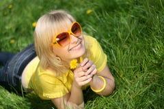 Jong meisje op een open plek van paardebloemen Royalty-vrije Stock Foto's