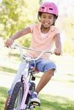 Jong meisje op fiets die in openlucht glimlacht Stock Fotografie