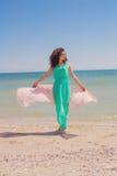 Jong meisje op het strand in de zomer met een vliegende sjaal Stock Foto's