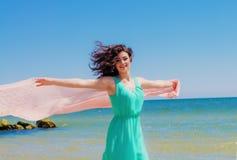 Jong meisje op het strand in de zomer met een vliegende sjaal Royalty-vrije Stock Fotografie