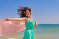 Jong meisje op het strand in de zomer met een vliegende sjaal Royalty-vrije Stock Foto