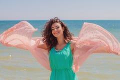 Jong meisje op het strand in de zomer met een vliegende sjaal Stock Afbeelding
