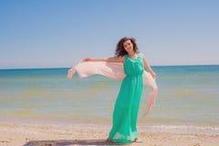 Jong meisje op het strand in de zomer met een vliegende sjaal Stock Foto
