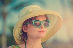 Jong meisje op het strand in groene glazen tijdens zonsondergang Royalty-vrije Stock Fotografie