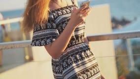 Jong meisje op het strand met uw smartphone Zonsondergang stock footage