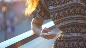 Jong meisje op het strand met uw smartphone Zonsondergang stock video