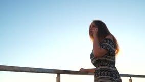 Jong meisje op het strand met uw smartphone Zonsondergang stock videobeelden