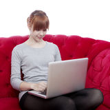 Jong meisje op rode bank die aan laptop werkt Stock Fotografie