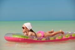 Jong meisje op roze luchtbed op Caraïbische vakantie Stock Afbeelding