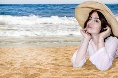 Jong meisje op strand in strohoed Stock Foto's