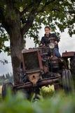 Jong meisje, oude tractor en oude eik Royalty-vrije Stock Fotografie
