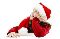 Jong meisje in rode Kerstmanhoed, die omhoog eruit ziet stock afbeeldingen