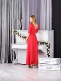 Jong meisje in rode kleding die zich dichtbij piano bevindt stock afbeelding